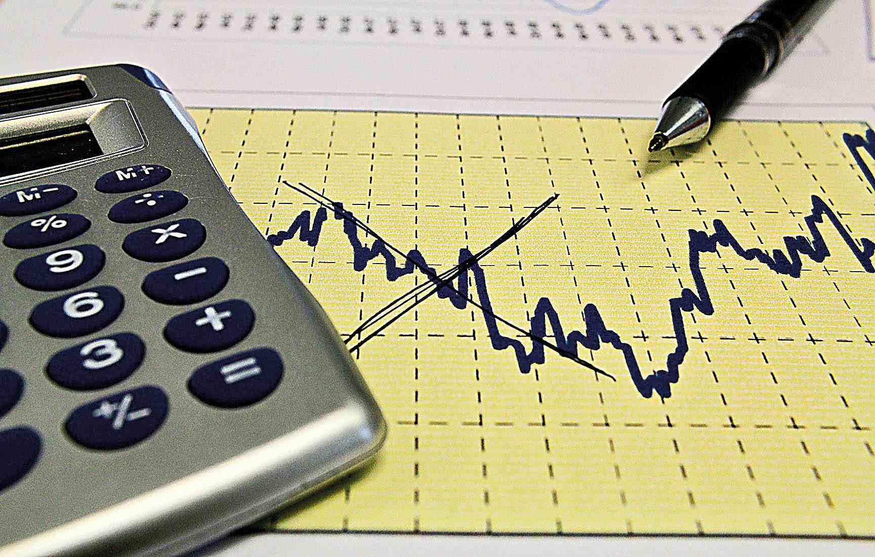 calculadora sobre papel amarelo com gráfico em queda desenhado