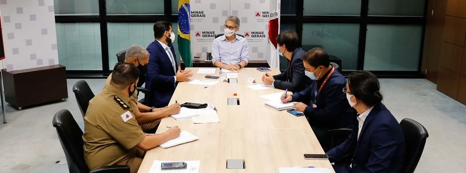 Governador de Minas, Romeu Zema, senta na ponta de uma mesa retangular com mais seis homens, sendo que cinco estão de terno e um de farda
