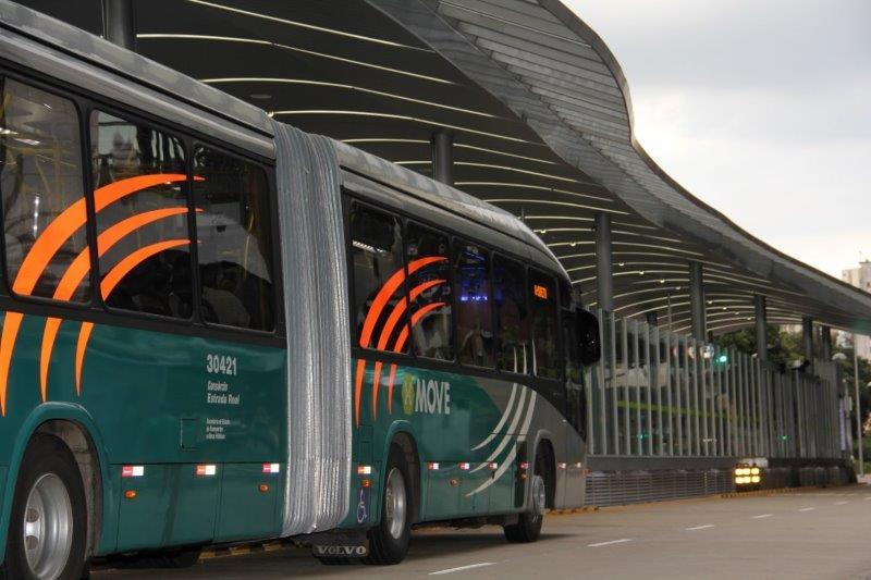Onibus metropolitano nas cores verde, cinza e laranja estaciona na estação de embarque de passageiros