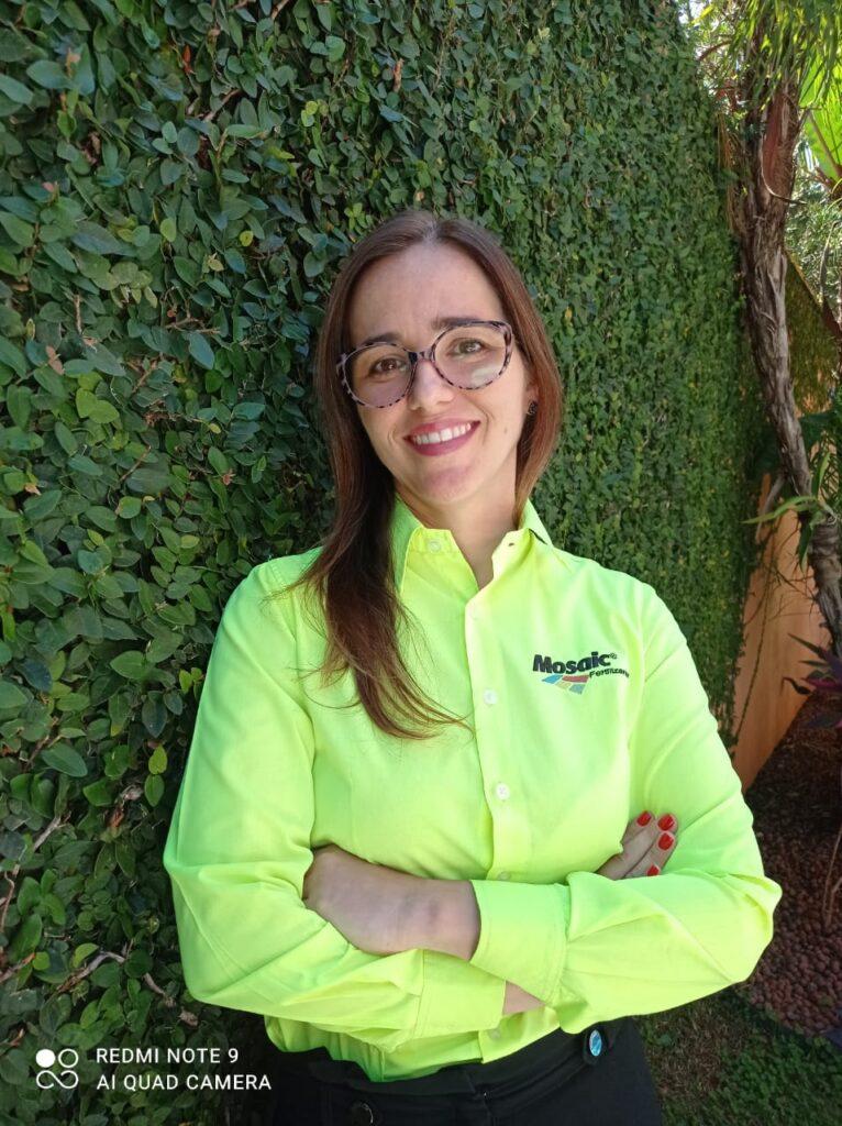 Mulher veste roupa verde e está escorada em muro coberto de plantas. Ela fala sobre o combate à fome