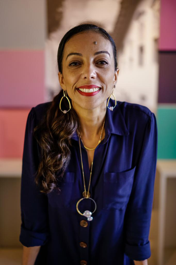 Mulher veste roupa cor azul escura, sorri e fala sobre o combate à fome