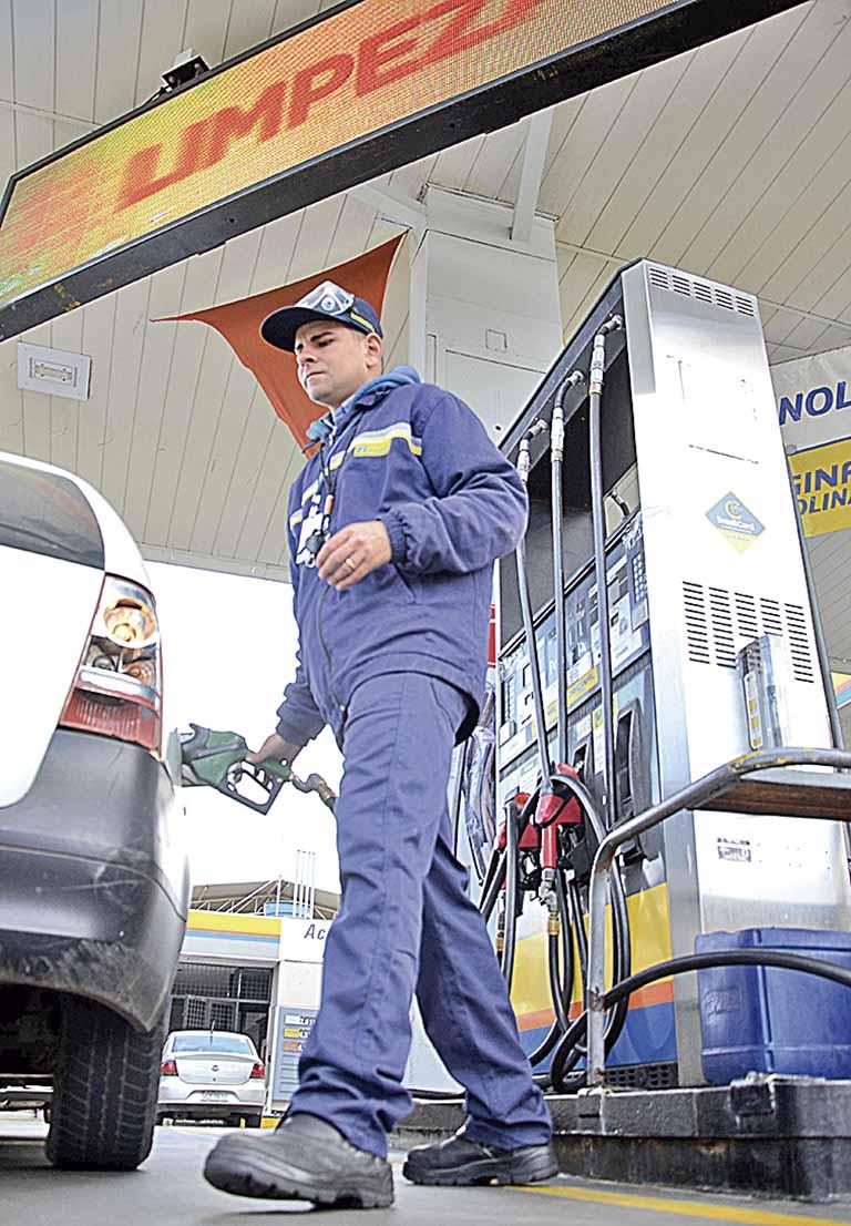 Frentista abastece carro em posto de gasolina