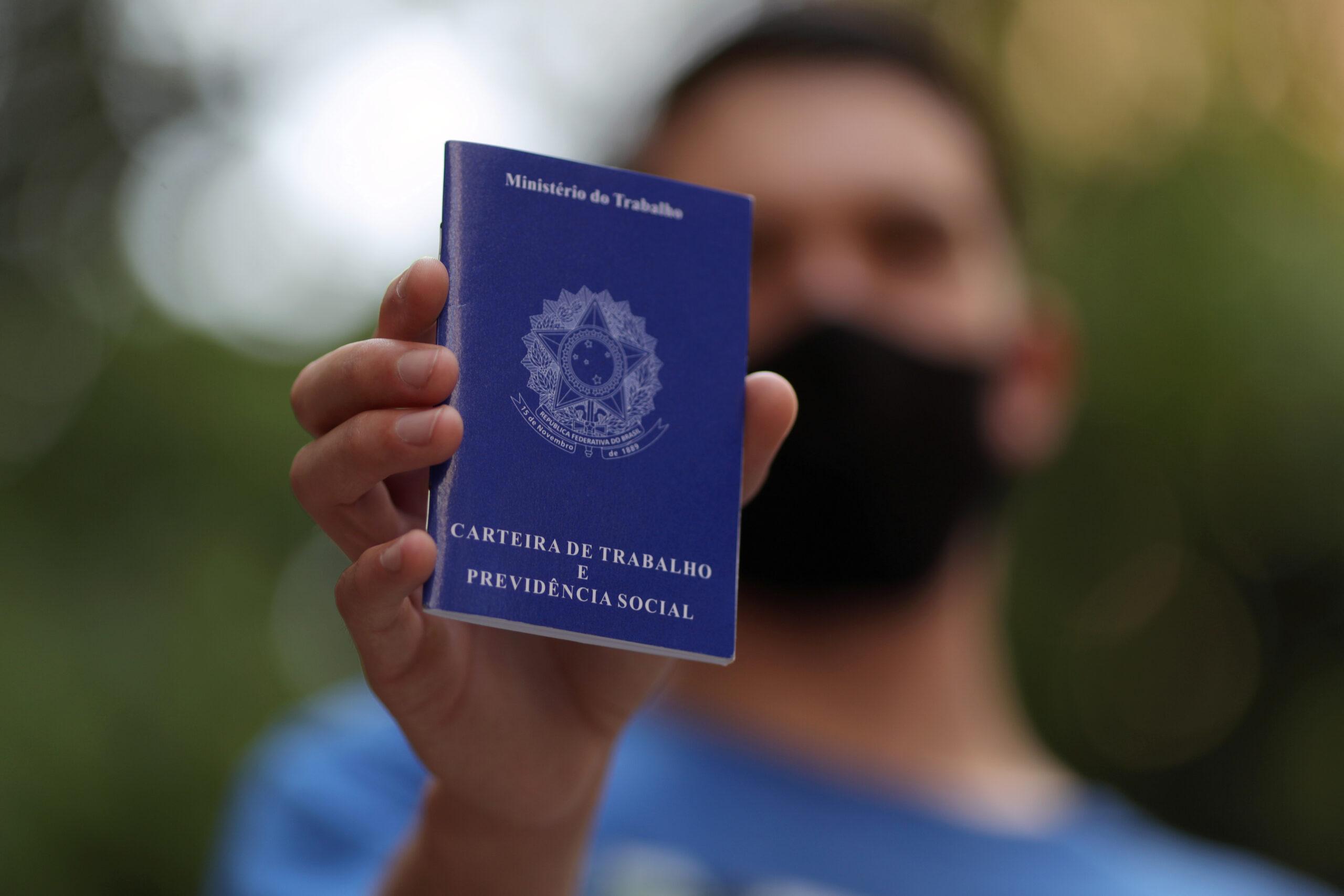 Homem mostra carteira de trabalho enquanto procura por oportunidades de emprego no centro de São Paulo