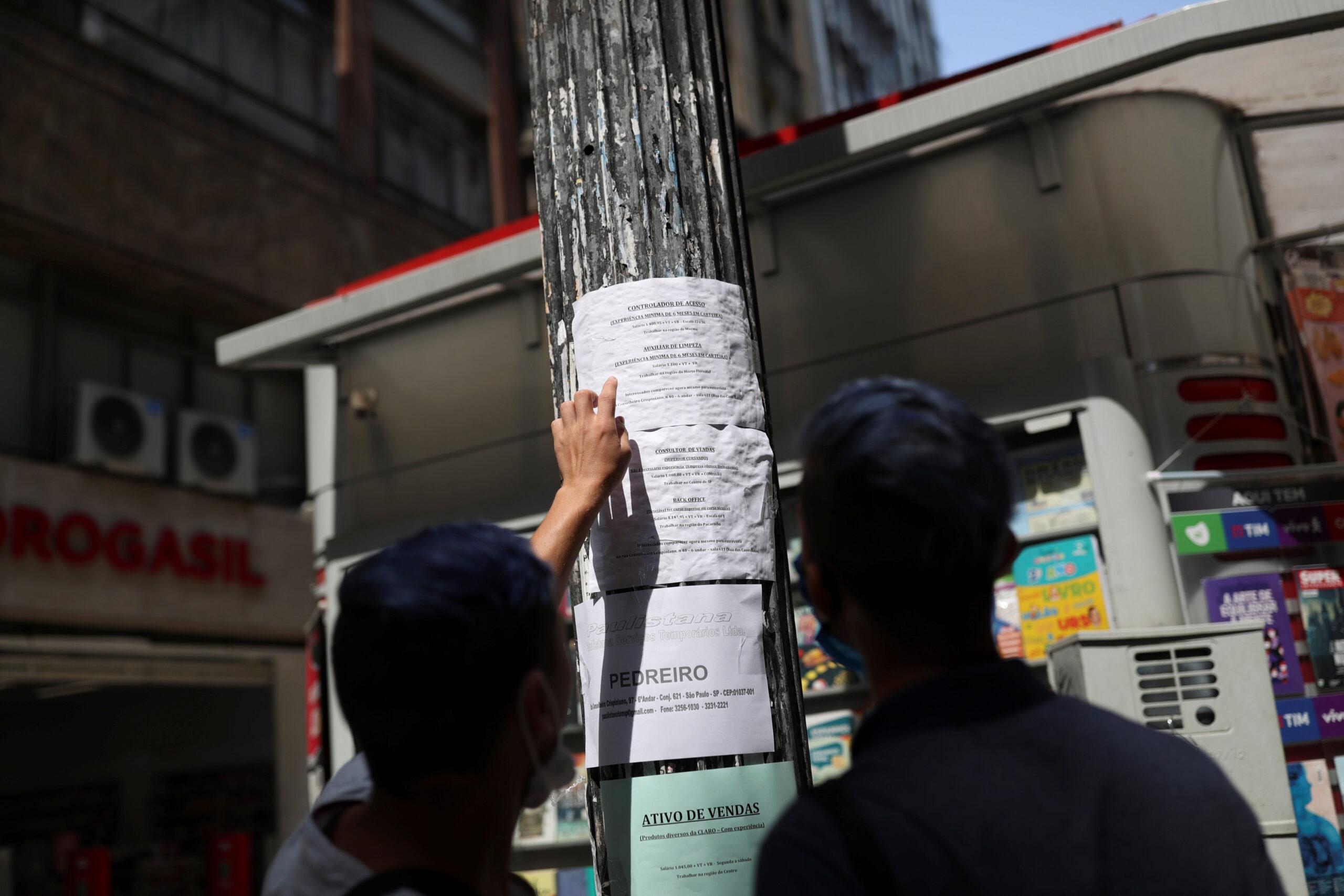 Pessoas avaliam oportunidades de emprego em cartaz no centro de São Paulo