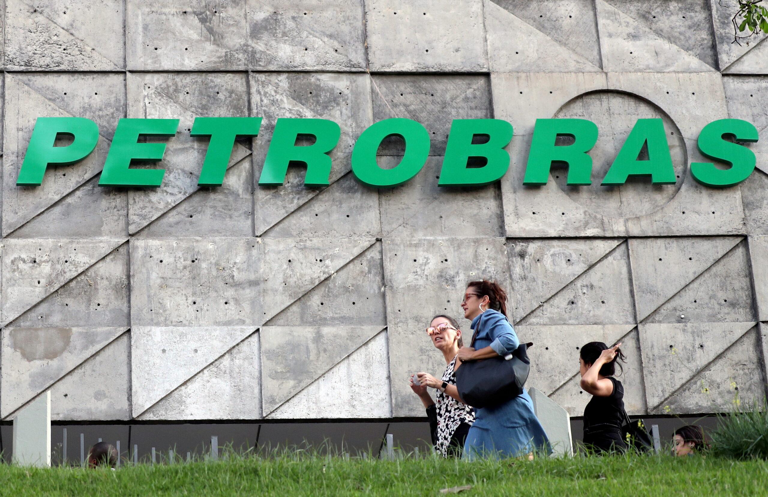 Pessoas caminham em frente a um prédio com o logotipo da Petrobras ao fundo