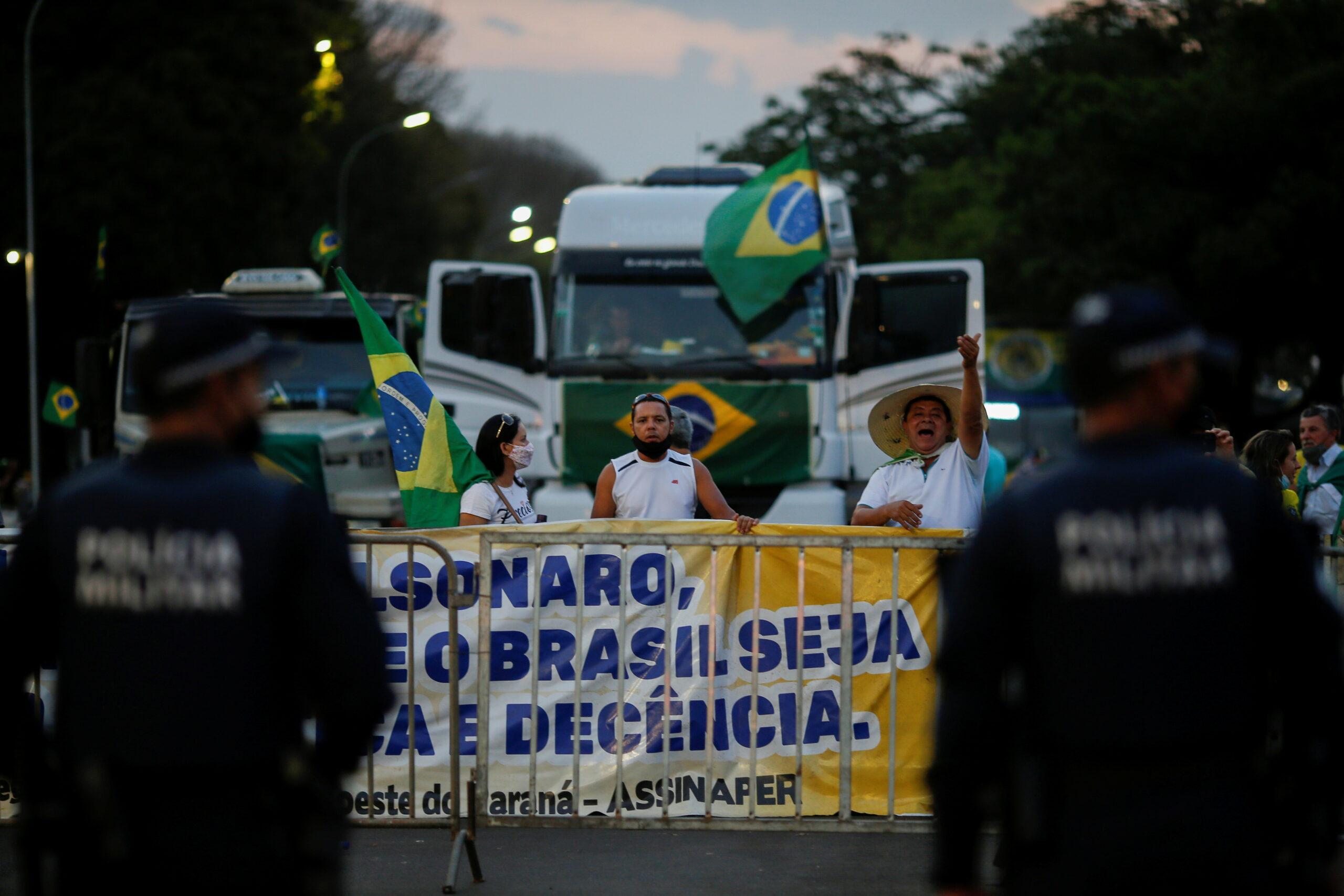 Pessoas estendem faixa como forma de protesto e caminhão ao fundo com bandeiras do Brasil