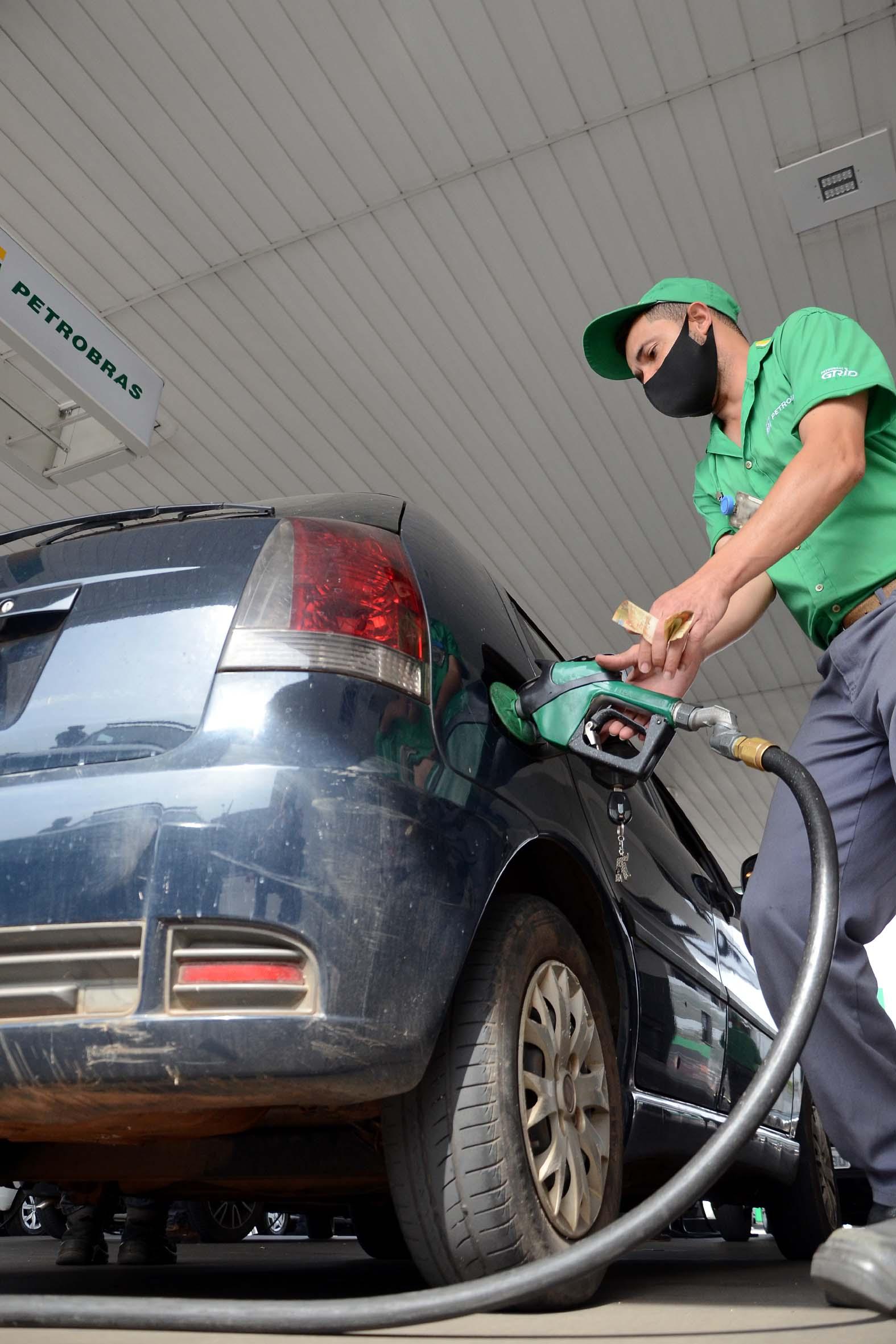 Frentista abastece carro em posto de combustível, localizado em Minas Gerais
