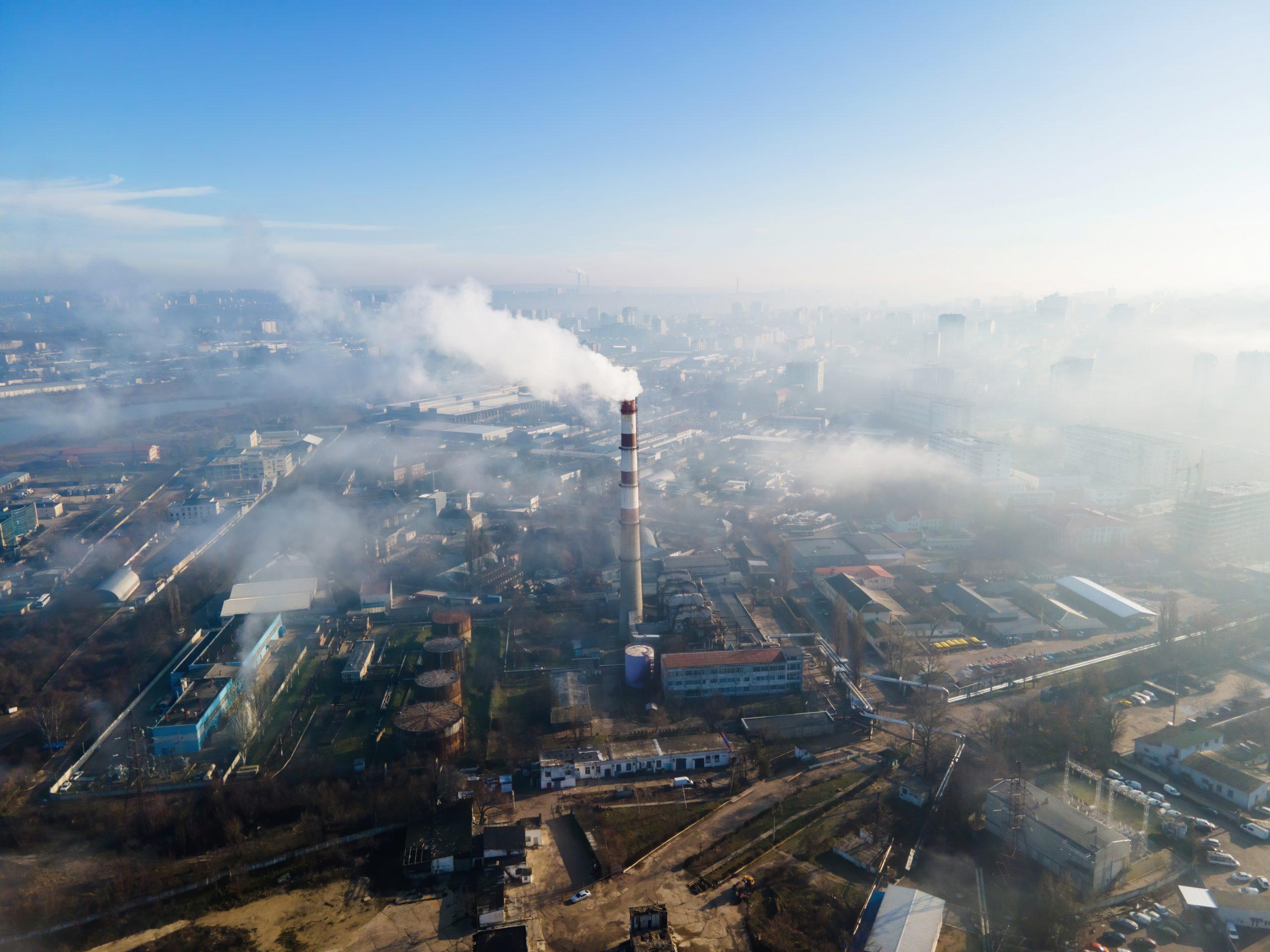 126 / 5000 Resultados de tradução Vista aérea do drone de Chisinau. Estação térmica com fumaça saindo do tubo. Edifícios e estradas. Nevoeiro no ar. Moldova