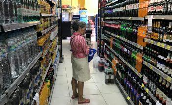 Mulher procura bebida em supermercado